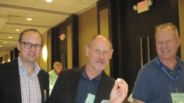 David Michaels (center) of Heritage holds a silver Athenian coin from before 500 B.C.E. (closeup at left) at CICF. He's accompanied by Ulrich Kuenker (left) of Germany and Cory Frampton of Mexican Coin Company.
