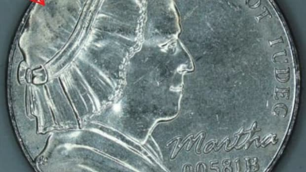 Martha Washington's portrait was used on test strikes of various compositions for the nickel. This one is multi-ply plated steel. The arrows indicate areas where planchet metal did not flow completely into the recesses of the die when struck under 54 tonnes to 60 tonnes pressure. Regular nickels are struck with 54 tonnes pressure.