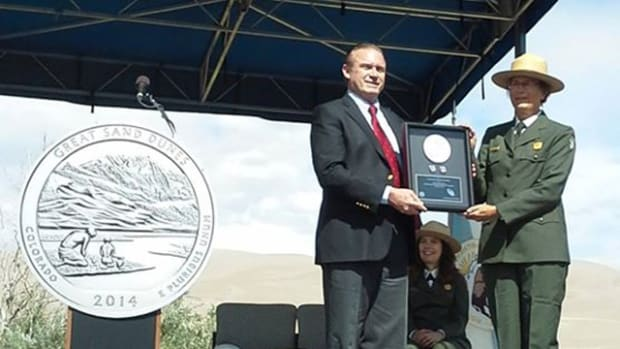 The Mint's Dave Croft presents first-day production quarters to park superintendent Lisa Carrico. at Great Sand Dunes National Park and Preserve.