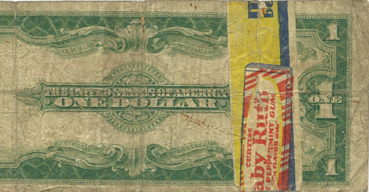 Fig. 3: This common 1923 $1 Silver Certificate entered the realm of unusual the moment someone used a sticky piece of 'Baby Ruth' gum advertising material to repair a tear.