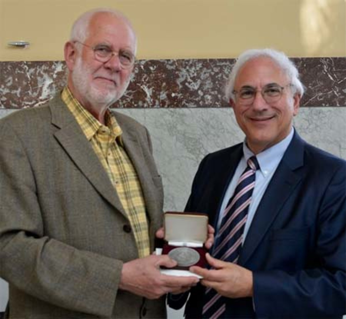 Geer Steyn, left, is presented with the J. Sanford Saltus Award by Donald Scarinci, right, chairman of the American Numismatic Society's Saltus Award Committee. (Image courtesy http://donaldscarinci.com)