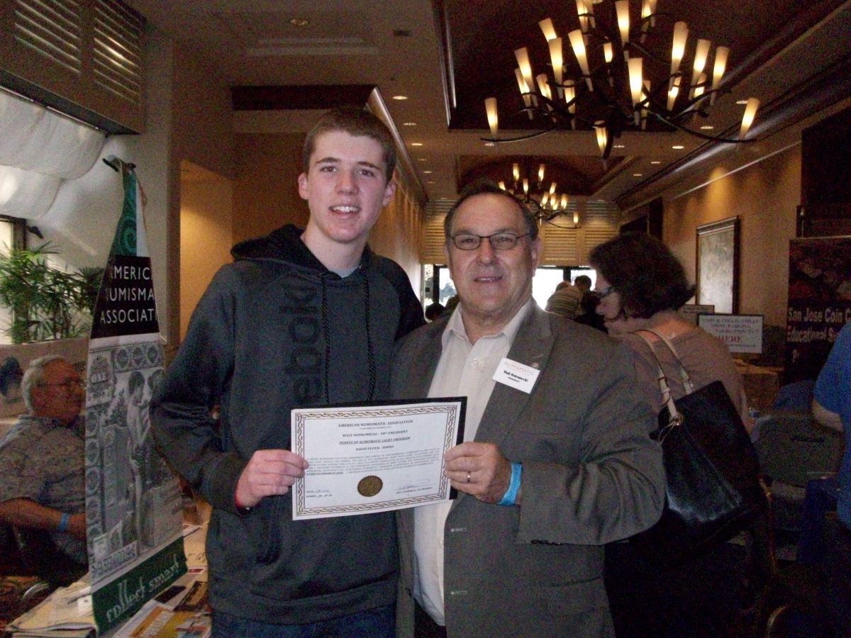 San Jose Coin Club Youth President Matthew Downing, receives a Point of Numismatic Light Award from ANA President Walter Ostromecki.