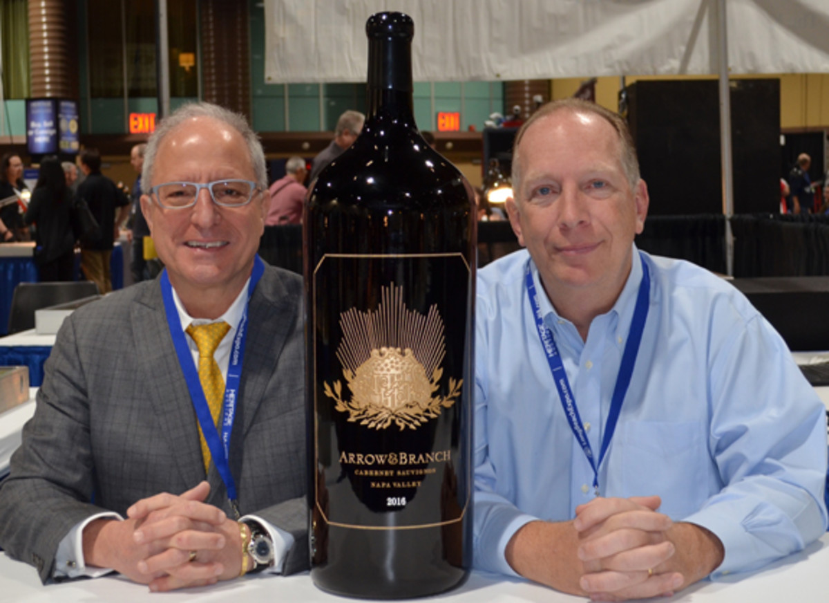 Steven L. Contursi (left) delivered the 60-pound bottle of Arrow&Branch wine to Lee Minshull (right) on Jan. 31, the first day of the Long Beach Coin, Currency, Stamp and Sports Collectibles Expo. (Donn Pearlman photo)