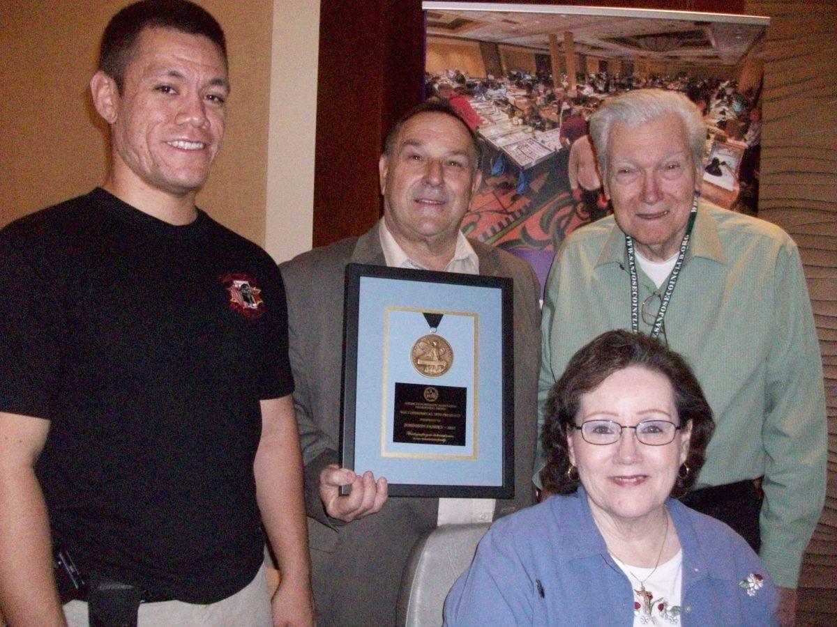ANA President Walter Ostromecki (center) presents an ANA Presidential Award to the Johnson Family, (from left) Ryan, Ray and Sally.