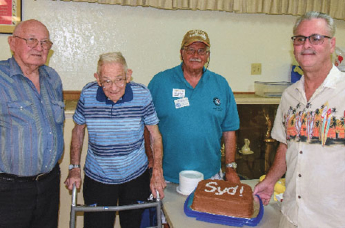 Ready to enjoy cake are, left to right, Dale Olson, Syd Kass at age 98, Michael S. Turrini, and Ed Hohe, current Delta Coin Club president.