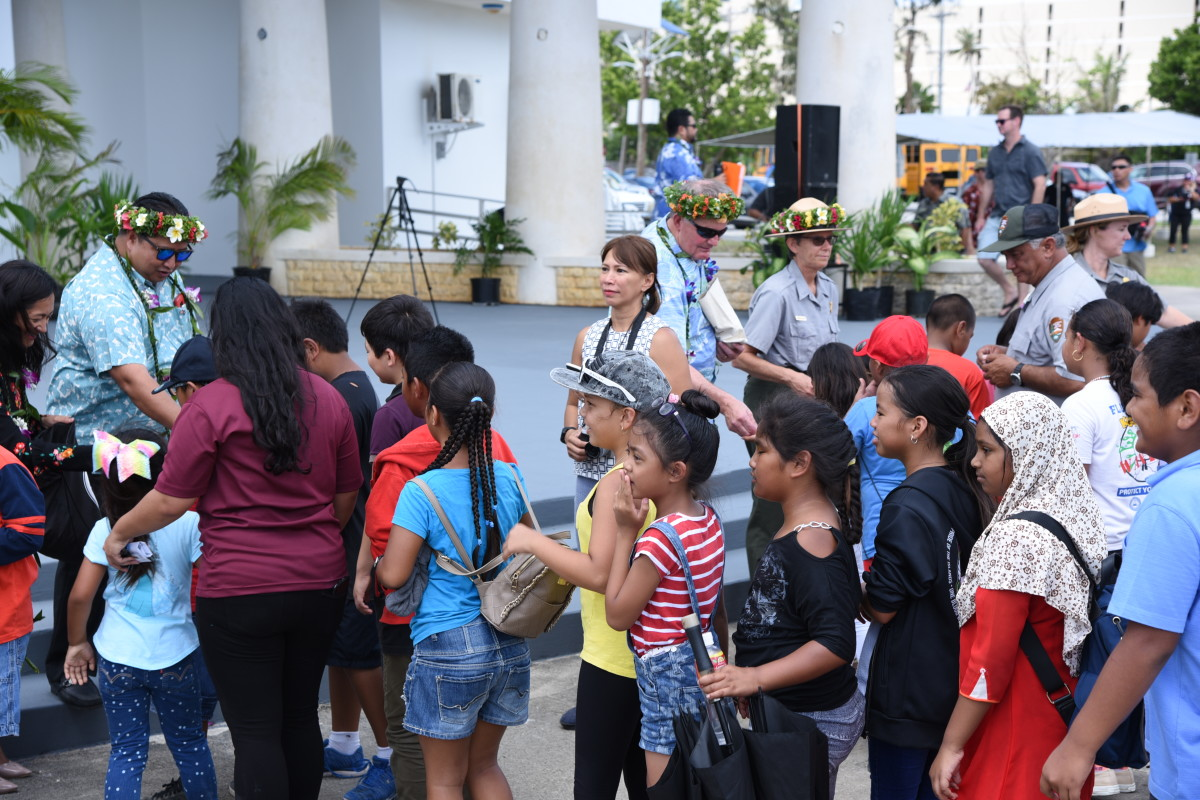 United States Mint Director David Ryder, Governor Ralph Torres, and American Memorial Park Superintendent Barbara Alberti, pass out new American Memorial Park quarters to children attending the launch ceremony April 30, 2019, in Garapan, Saipan.  More than 1,000 school children attended, along with 200 other coin enthusiasts. U.S. Mint photo by Sharon McPike.