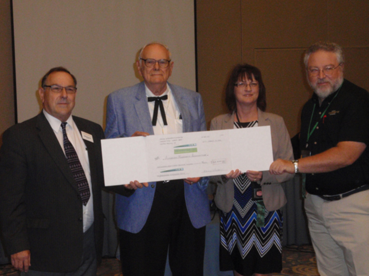 From left, Walter Ostromecki, Gerome Walton, Kim Kiick and Rod Gillis pose with a facsimile check for $163,000 given for college scholarships.