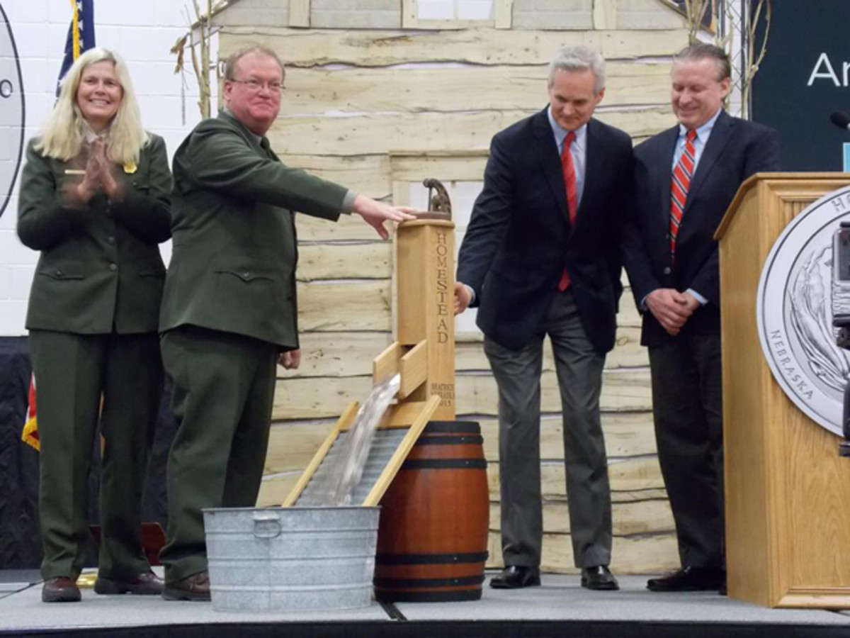 From left, Patty Trap, Mark Engler, Mike Foley and David Croft join for a ceremonial coin pour to officially launch the Homestead National Monument of America quarter.