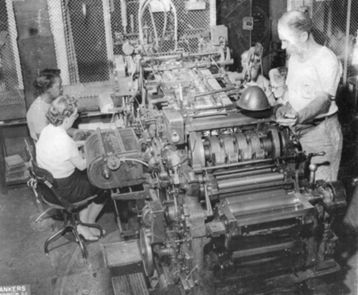This is a 12-subject serial numbering and sealing press of the type that produced the $1 1935A mismatch treated here. The machines were manufactured by the Miehle Printing Press and Manufacturing Co. of Chicago and had a capacity of 4,200 sheets per hour. The feed stock was loaded in a bin behind the machine and each sheet was picked up and fed into the press by suction devices at the ends of the vacuum hoses at the top of the photo. The two pairs of women on the sides of the machine received the cut and collated notes from the respective sides of the sheets, and arranged the notes for inspection and packaging. Notice that the press and all the personnel are indeed inside a cage. (BEP Historical Resource Center photo)