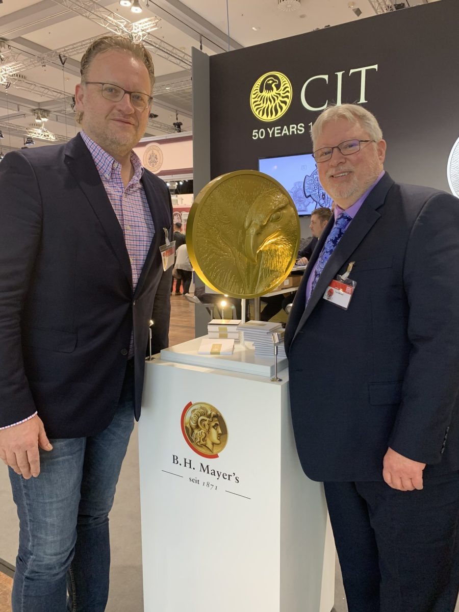 Alex Wegner, owner and managing director of B. H. Mayer's (left) and Tom Michael, Coin of the Year coordinator, bookend a lovely Smartminting Reloaded display at the CIT booth during World Money Fair 2020.