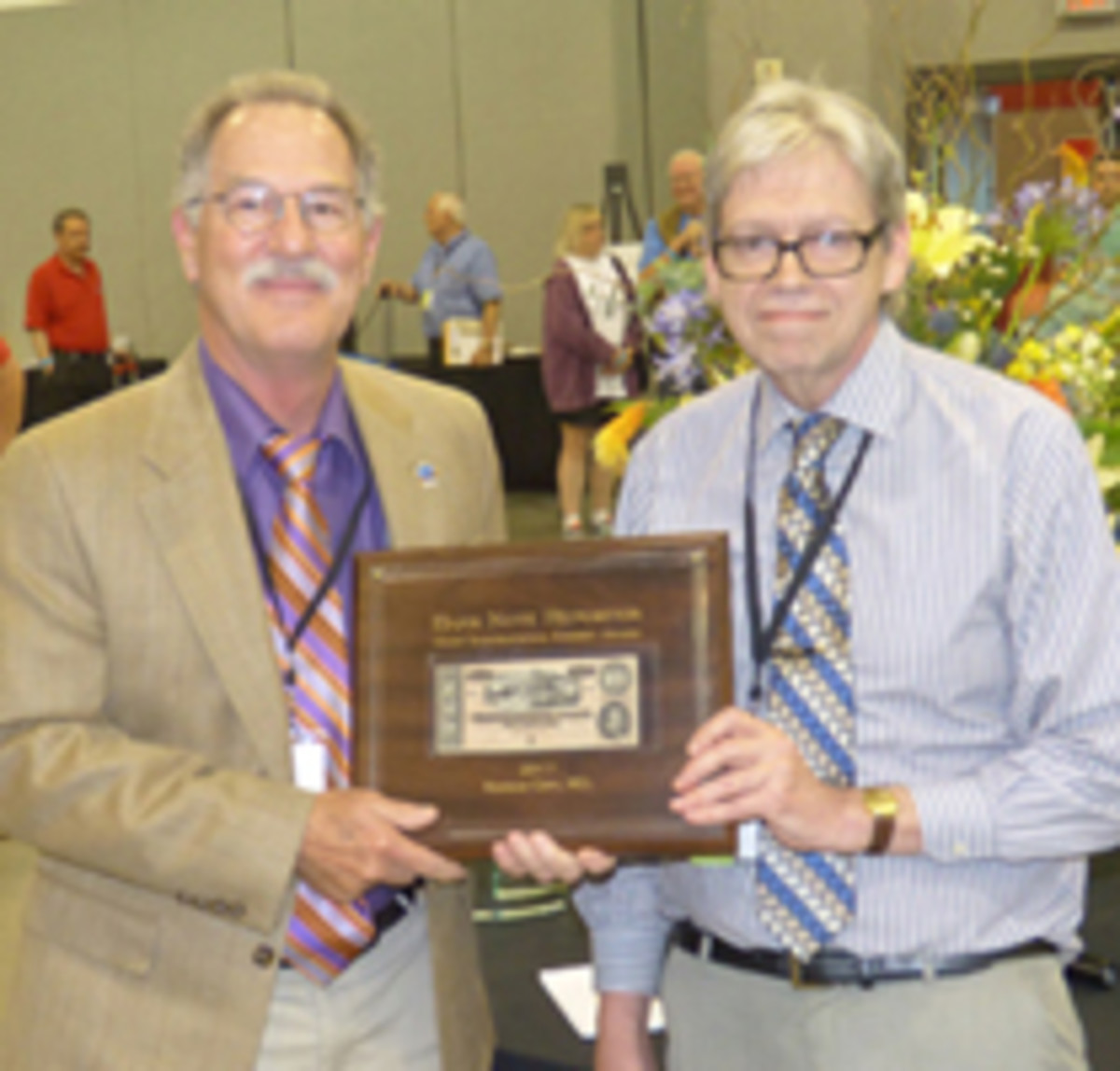 Michael McNeil, left, won the Bank Note Reporter Most Inspirational Exhibit Award. Presenting is BNR editor Robert R. Van Ryzin.
