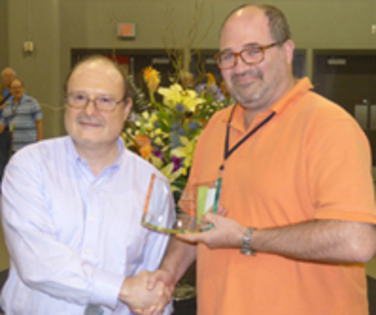 Andrew Shiva, right, accepts the Society of Paper Money Collectors Founders Award from outgoing SPMC president Pierre Fricke.