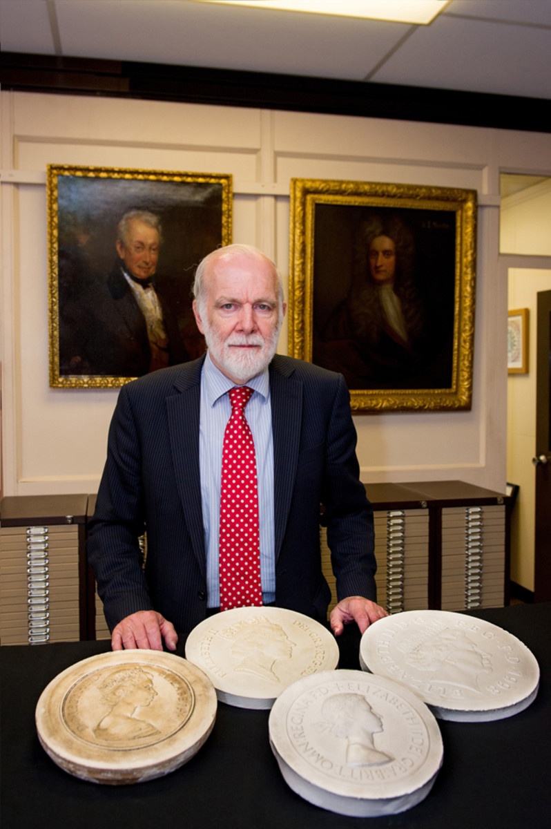 Doyen of Britain's Royal Mint Graham Dyer with the plasters of the first four coinage portraits of Queen Elizabeth II. Image courtesy of an © The Royal Mint.