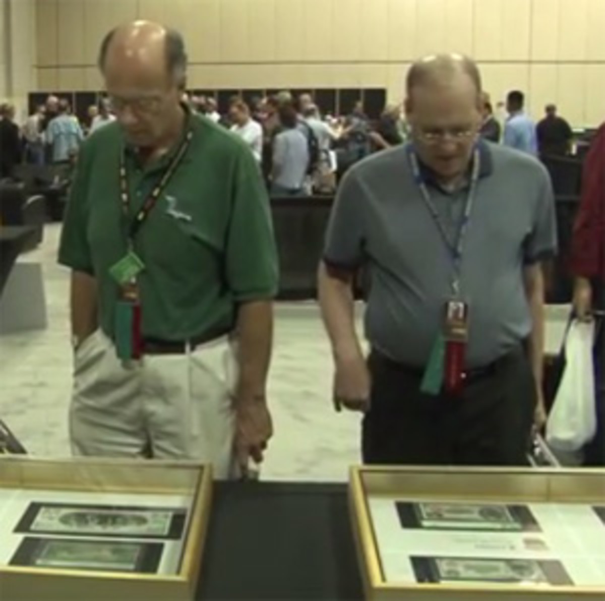 Attendees of the 2014 International Paper Money Show examine an exhibit. (Image courtesy https://coinweek.com)