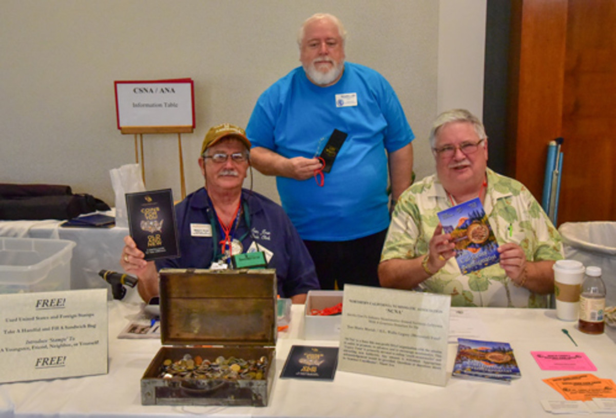Staffing the combination table: seated Michael S. Turrini and James H. Laird with Donald L. Hill, standing. They display information and items available at the table.