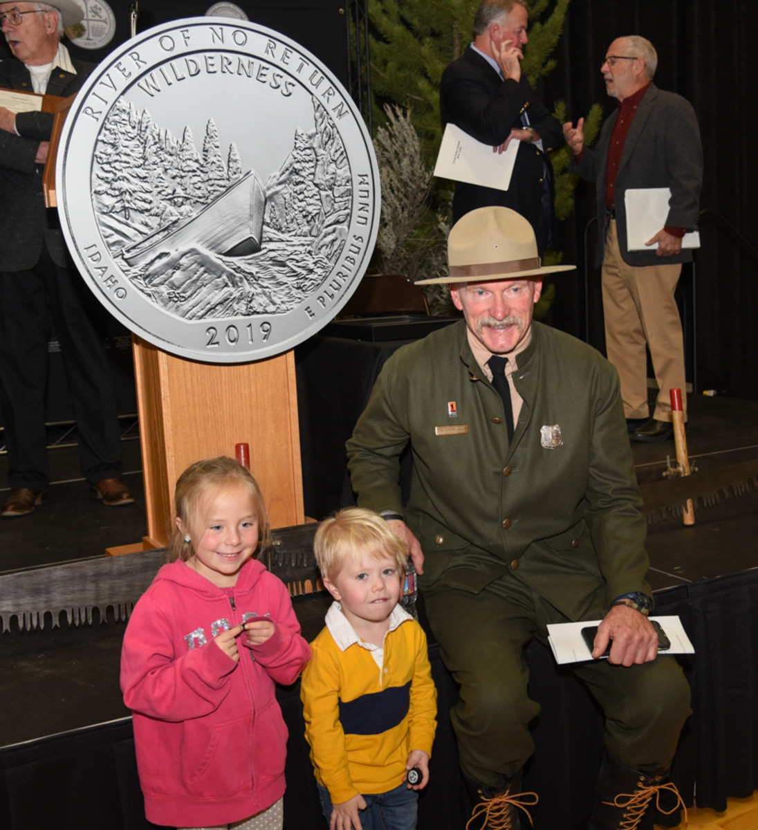 Two youngsters hold new Frank Church River of No Return Wilderness quarters and pose for a photo with Charles Mark, forest supervisor, Salmon-Challis National Forest. (U.S. Mint photo by Jill Westeyn.)