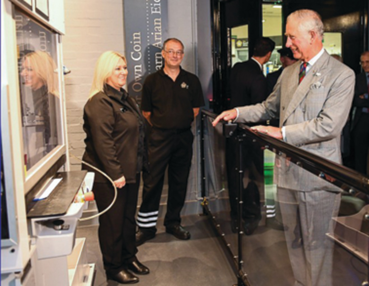 Prince Charles strikes the first commemorative £5 coin of his father at Britain's Royal Mint. (Image courtesy & © The Royal Mint)