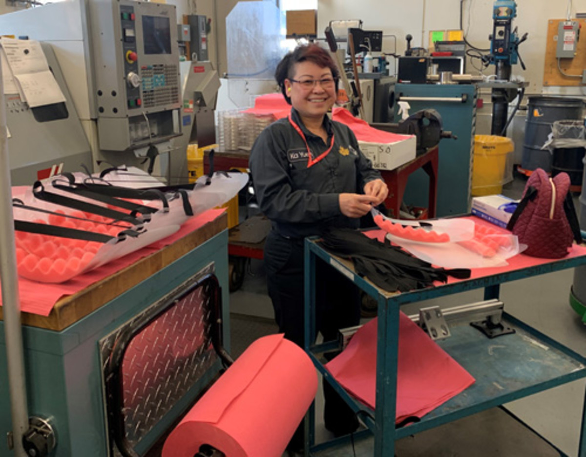 More than 1,893 medical face shields were produced through mid-May at the Royal Canadian Mint's Ottawa facility for use by local health care workers. Here we see production employee Ka Yuen assembling face shields. (Image courtesy Royal Canadian Mint.)