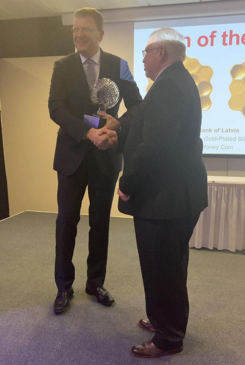 Jānis Blūms of the Bank of Latvia (left) accepts the Coin of the Year award from Tom Michael.