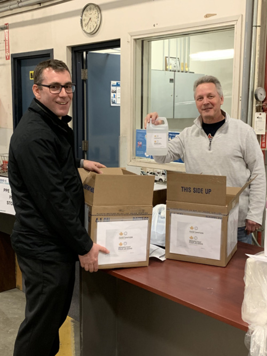 Brad Everton, senior manager of applied research in Winnipeg, hands over a batch of Mint-manufactured hand sanitizer to Geoff Enns of the Manitoba Government. (Image courtesy Royal Canadian Mint.)