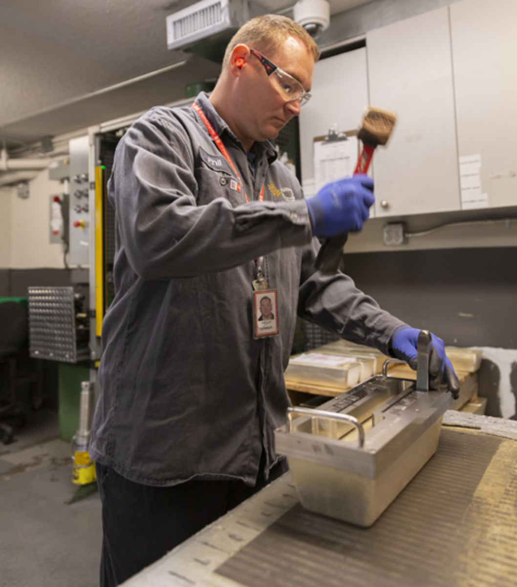 Refinery employee Phillip Downer stamps a 1,000-ounce silver bar at the Royal Canadian Mint in Ottawa. Downer has worked throughout the pandemic as the RCM re-prioritized operations to focus on bullion in support of the mining industry and financial sector. (Image courtesy Royal Canadian Mint.)