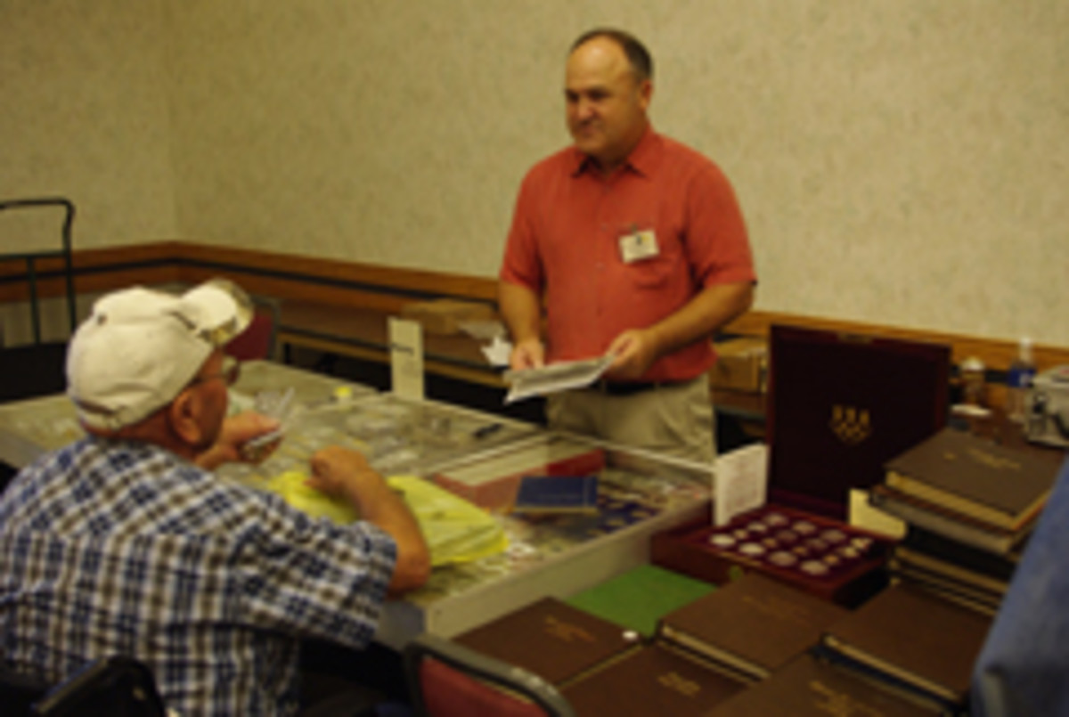 Gene Murren of Gene Murren Coins & Precious Metals of Longmont, Colo., talks to a collector at the 8th annual Wyo-Braska Coin & Stamp Collector Show Sept. 13 in Gering, Neb. (Photo by Mitch Ernst)