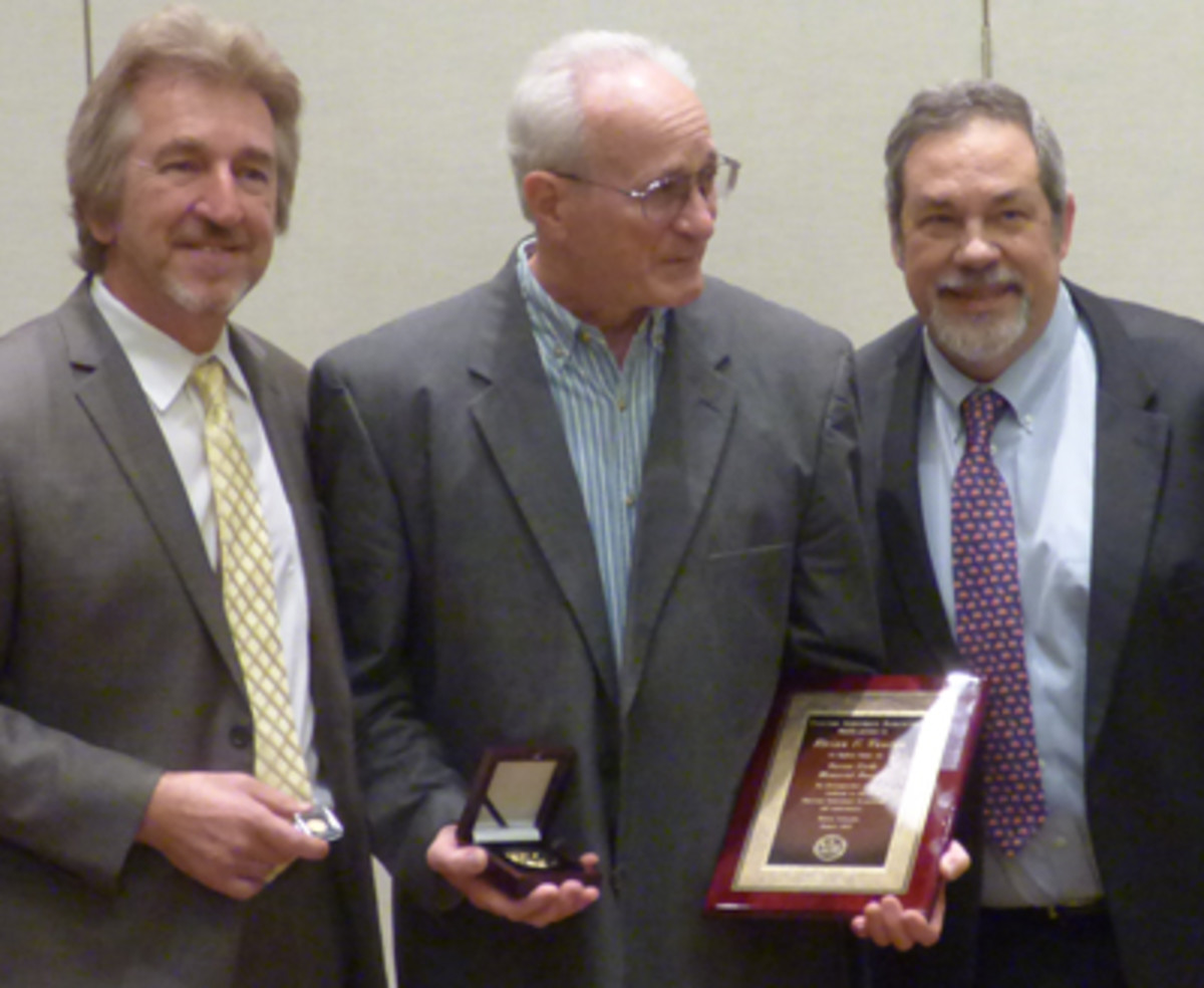 Outgoing ANA President Jeff Garrett, left, and Mike Fuljenz, CEO of Universal Coin & Bullion, right, present the Farran Zerbe Memorial Award to Brian Fanton.