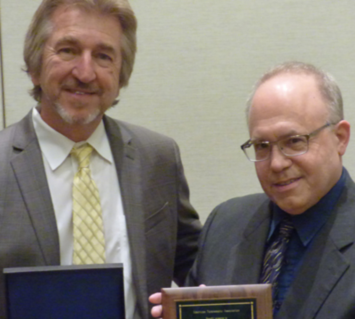 David W. Lange, right, accepts the Numismatist of the Year Award from Jeff Garrett.