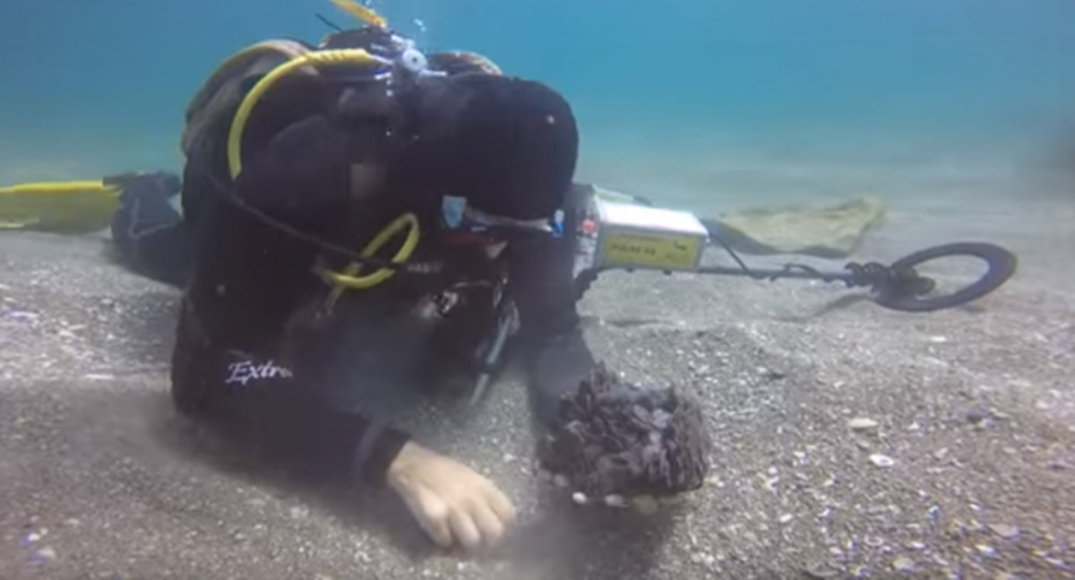 A scuba diver recovers ancient Roman coins from the discovered shipwreck. (Image by Assaf Pereti, Israel Antiquities Authority)