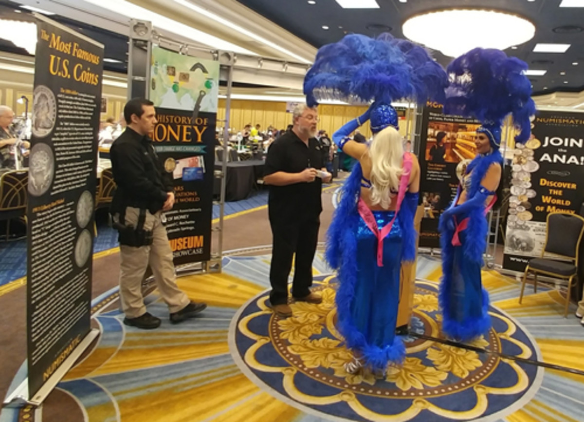ANA Education Director Rod Gillis talks about the King and Queen of Coins with two Westgate Resort Hotel Las Vegas showgirls in costume.