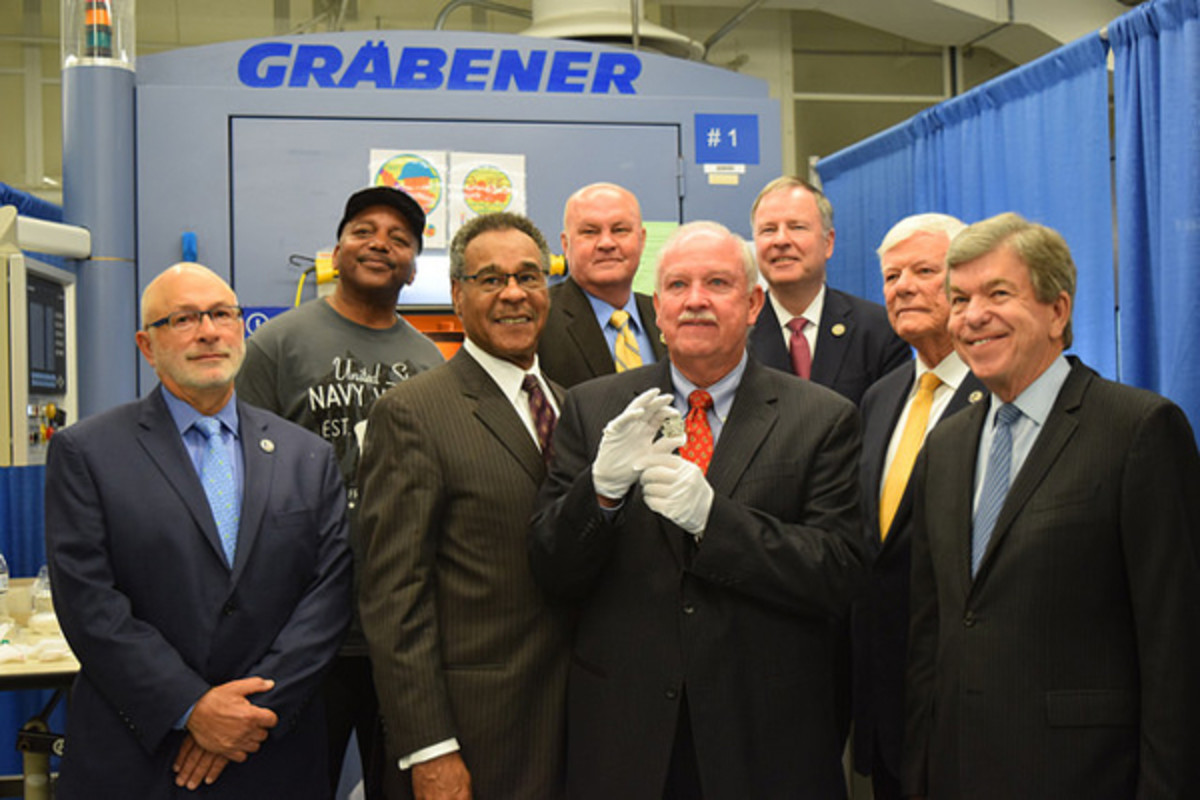 Gerald York, grandson of World War I hero Sergeant Alvin York, holds a newly minted 2018 World War I Centennial Silver Dollar. He is joined by (left to right) Daniel Basta, U.S. Foundation for the Commemoration of the World Wars, U.S. Mint Coin Press Operator Kenneth Holland, Rep. Emanuel Cleaver II, D-Mo., U.S. Mint Police Chief Dennis O'Connor, Rep. Doug Lamborn (R-Colorado), U.S. World War I Centennial Commission Chair Terry Hamby and Sen. Roy Blunt, R-Mo.. The commemorative coin will be released on Jan 17, 2018. (U.S. Mint photo by Sharon McPike)