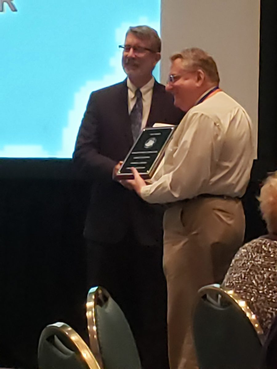 Patrick Heller accepts one of the two awards he won at the 2019 Numismatic Literary Guild Awards banquet on August 15, 2019.