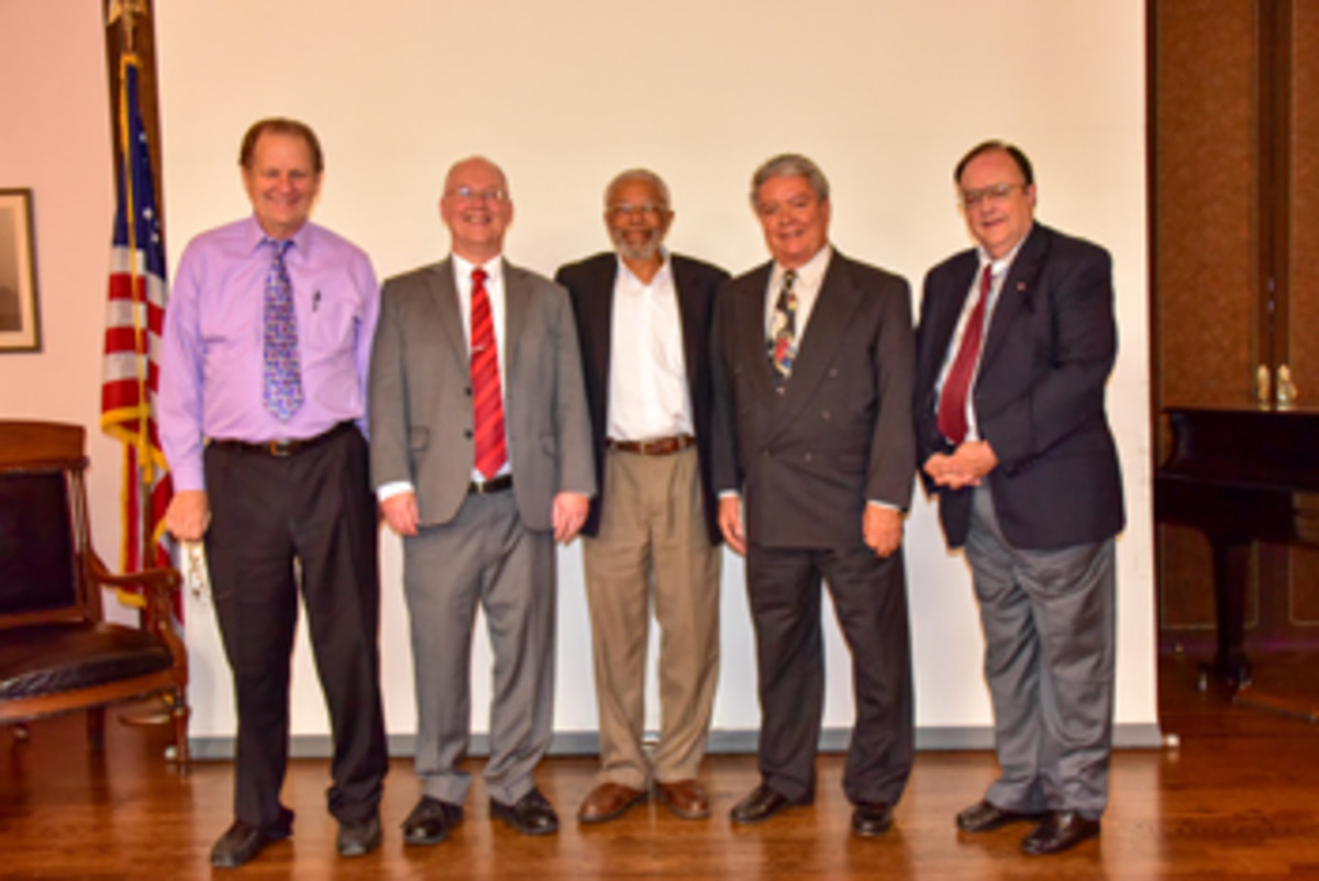 The four speakers shared the stage with moderator Herbert Miles, center.