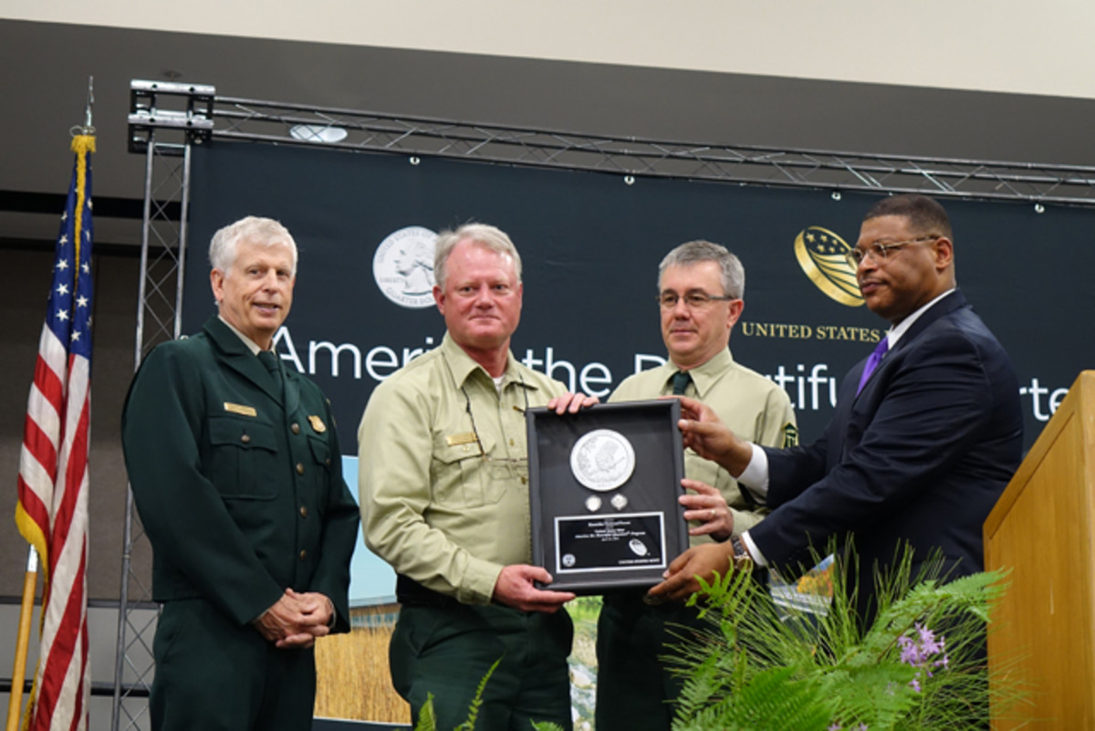 B.B. Craig, right, presents Kisatchie National Forest quarters struck on the first day of production to, left to right, U.S. Forest Service Chief Thomas Tidwell, Regional Forester Tony Tooke, and Kisatchie National Forest Supervisor Eddie Taylor. (U.S. Mint photo by Sharon McPike.)