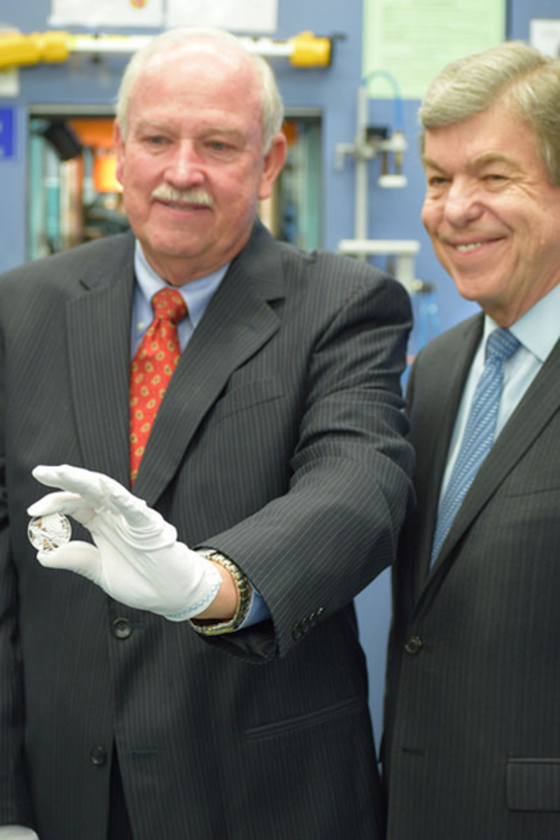 A clearly pleased Sen. Roy Blunt grins for the camera, right, as Gerald York holds up his handiwork in the first strike of the World War I silver dollar. (U.S. Mint photo by Sharon McPike)