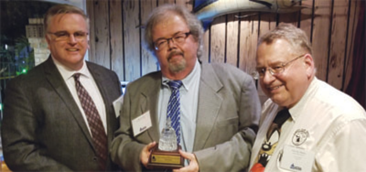 Industry Council for Tangible Assets chief operating officer David Crenshaw, left, and ICTA treasurer Patrick Heller, right, present Phil Darby with the organization's Diane Piret Memorial Outstanding Service Award.