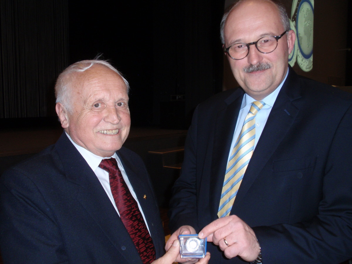 Albert Beck, left, receives a new polymer-ringed German 5 euro from Dr. Michael Meister.