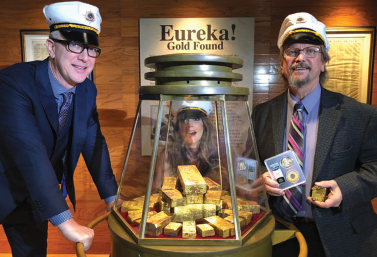 """Dwight Manley, KTLA-TV reporter Christina Pascucci (peering from behind the display) and Bob Evans at """"Goldhenge,"""" a display of 35 of the 45 retrieved """"SS Central America"""" gold ingots from the 2014 recovery mission. (Photo courtesy of Dwight Manley.)"""