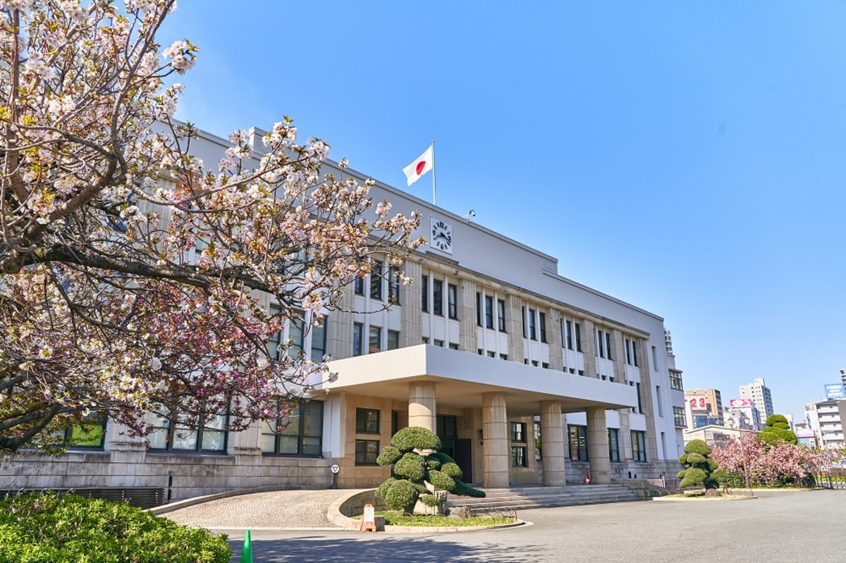 With columns out front, sculpted shrubs and cherry blossoms flanking, the head office of the Japan Mint cuts a striking figure of a classic government style structure, combining functionality and beauty.
