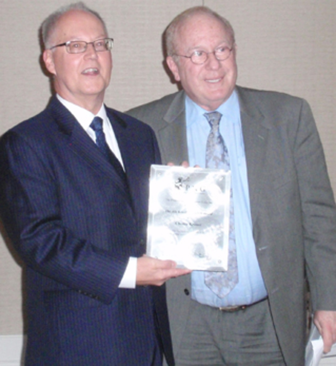 Dave Harper (left) accepts the Abe Kosoff Founders Award honoring the late Chet Krause from PNG Vice President Barry Stuppler.