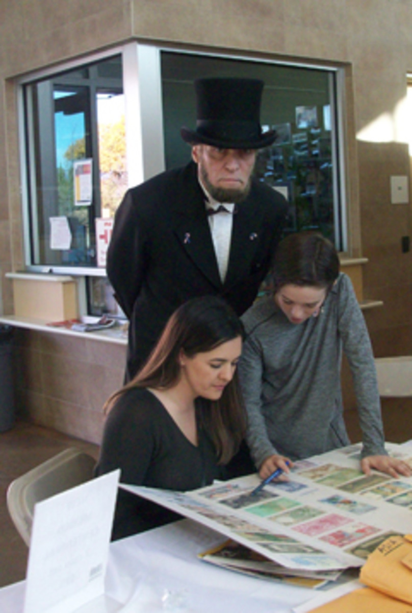 President Lincoln provides advice to a mother and son working on the world currency country match challenge in the Kid's Zone activity area.