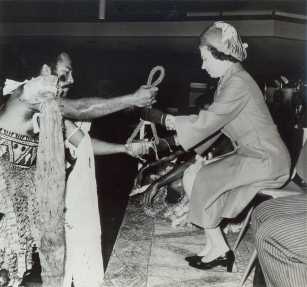 Queen Elizabeth II is presented with and accepts a tabua during a ceremonial presentation at the Commonwealth Institute in Kensington in 1974, thus binding her and the Fijian people together. Image courtesy Omega Collection.