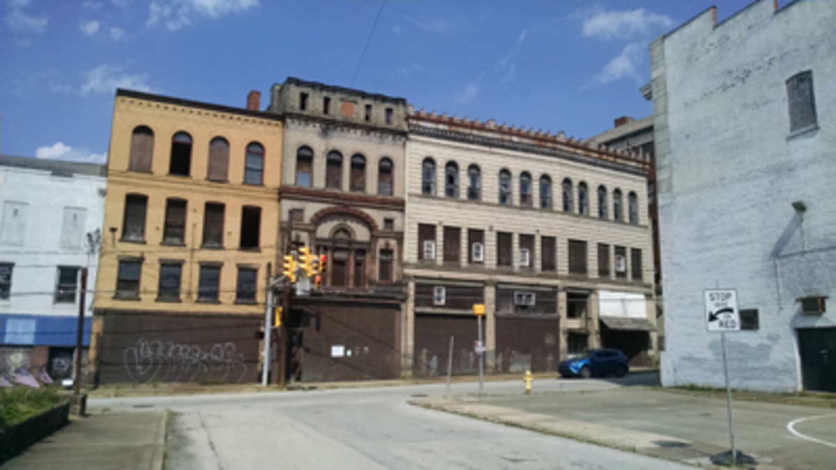 This row of abandoned but classic storefronts sits across Market Street from the Monongahela National Bank, whose wall is at right. The parking area in foreground once was filled with similar commercial structures.