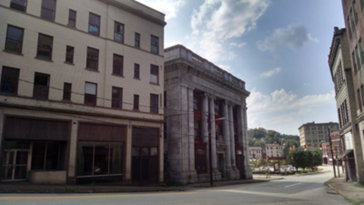 A little further down Market Street, past abandoned storefronts, the colonnaded Monongahela National Bank of Brownsville sits abandoned. In the distance, atop the little hill, is the National Deposit Bank.