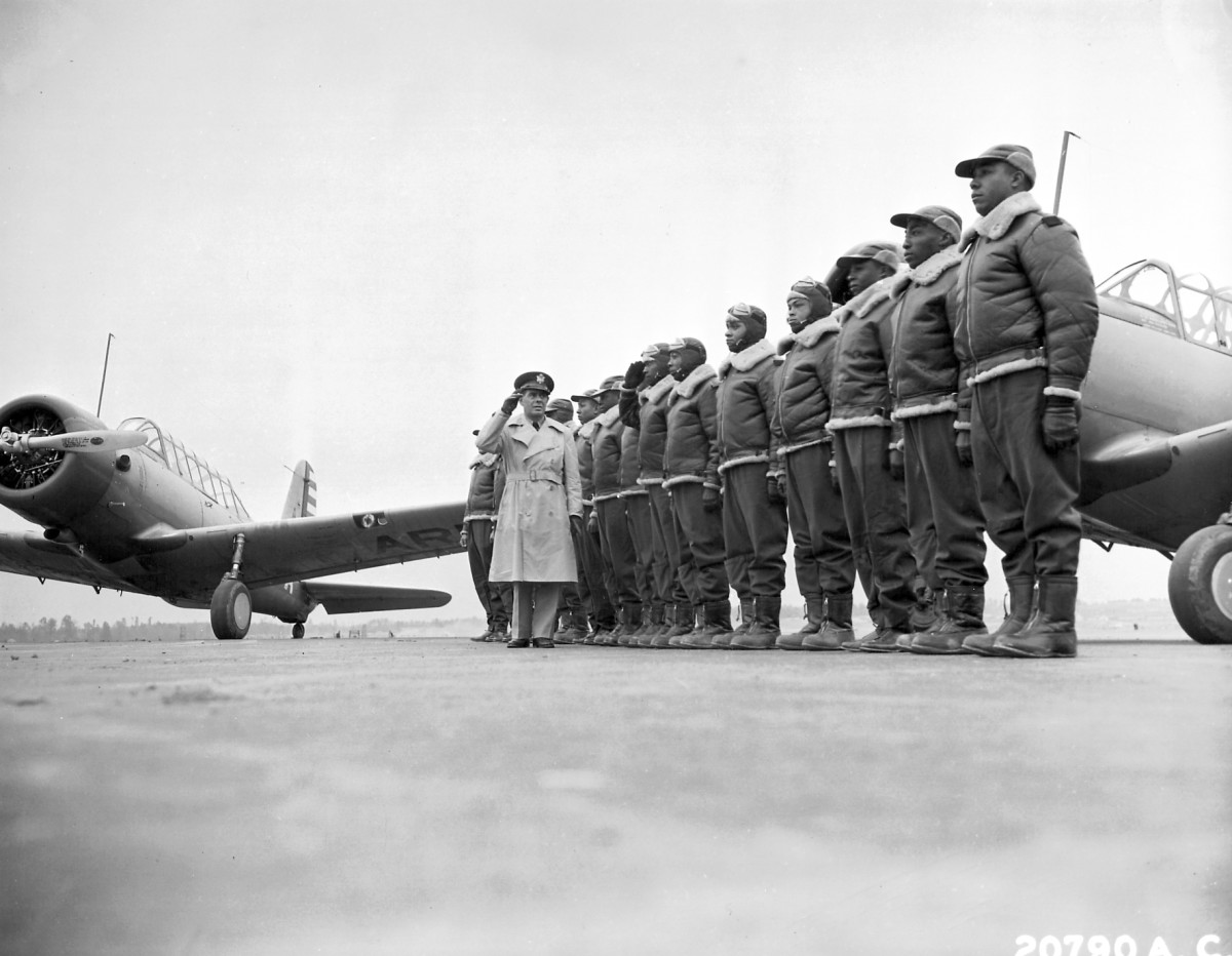 Major James A. Ellison reviews first class of Tuskeegee Airmen, returning the salute of Mac Ross, one of the first graduates. A BT-13 is visible on the left. Date: 1941. (Image courtesy Wikimedia Commons.)