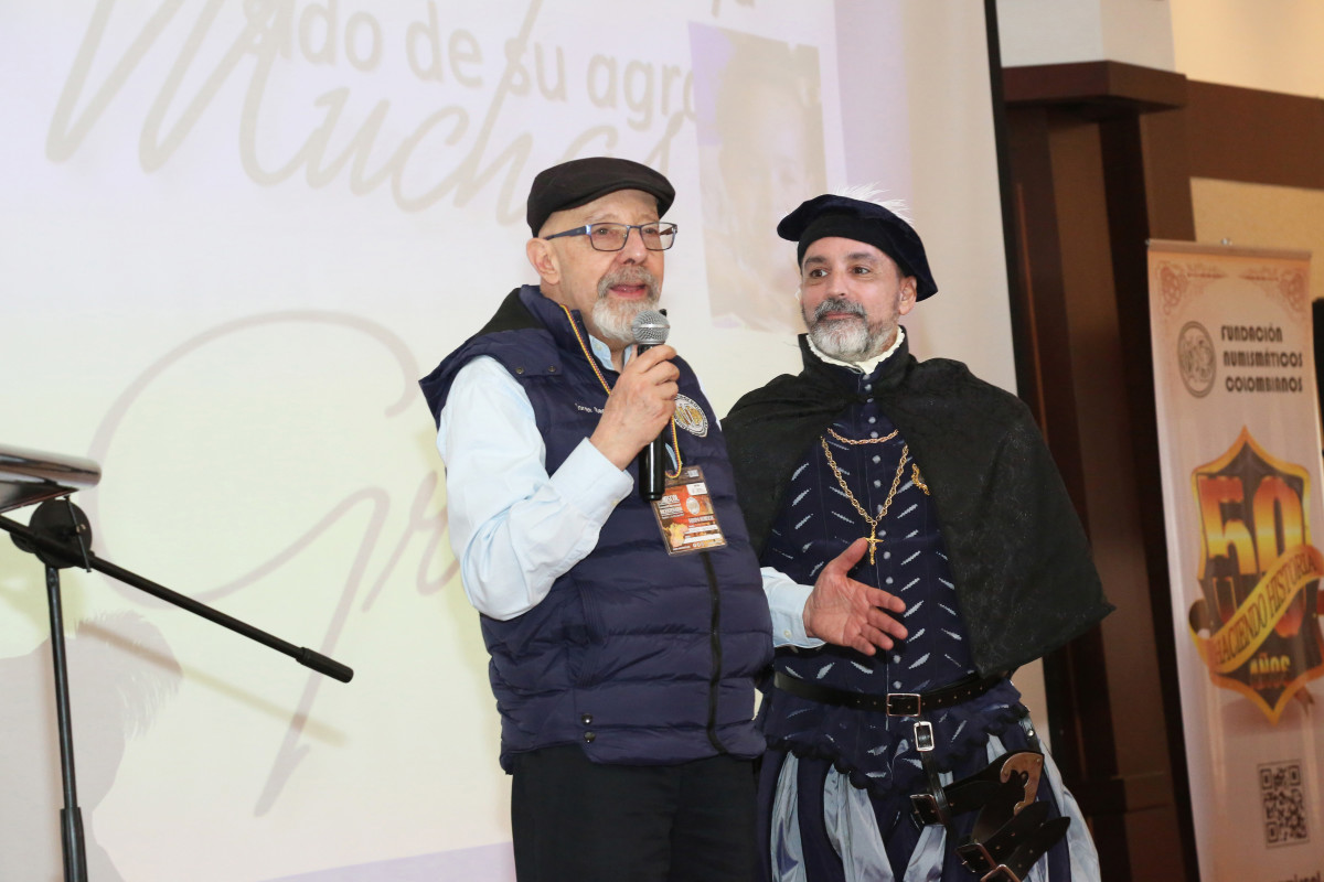 Noted Colombian historian, numismatist, and San José shipwreck expert Jorge Becerra de Leon, left, and historic research expert/numismatist Jorge Proctor, in period costume, address an audience at a previous conference. Both will be featured speakers at Cartagena MMXXI – the 3rd International Convention of Historians and Numismatists, taking place Dec. 1-5, 2021, in Cartagena, Colombia. (Photo by Carol Tedesco)