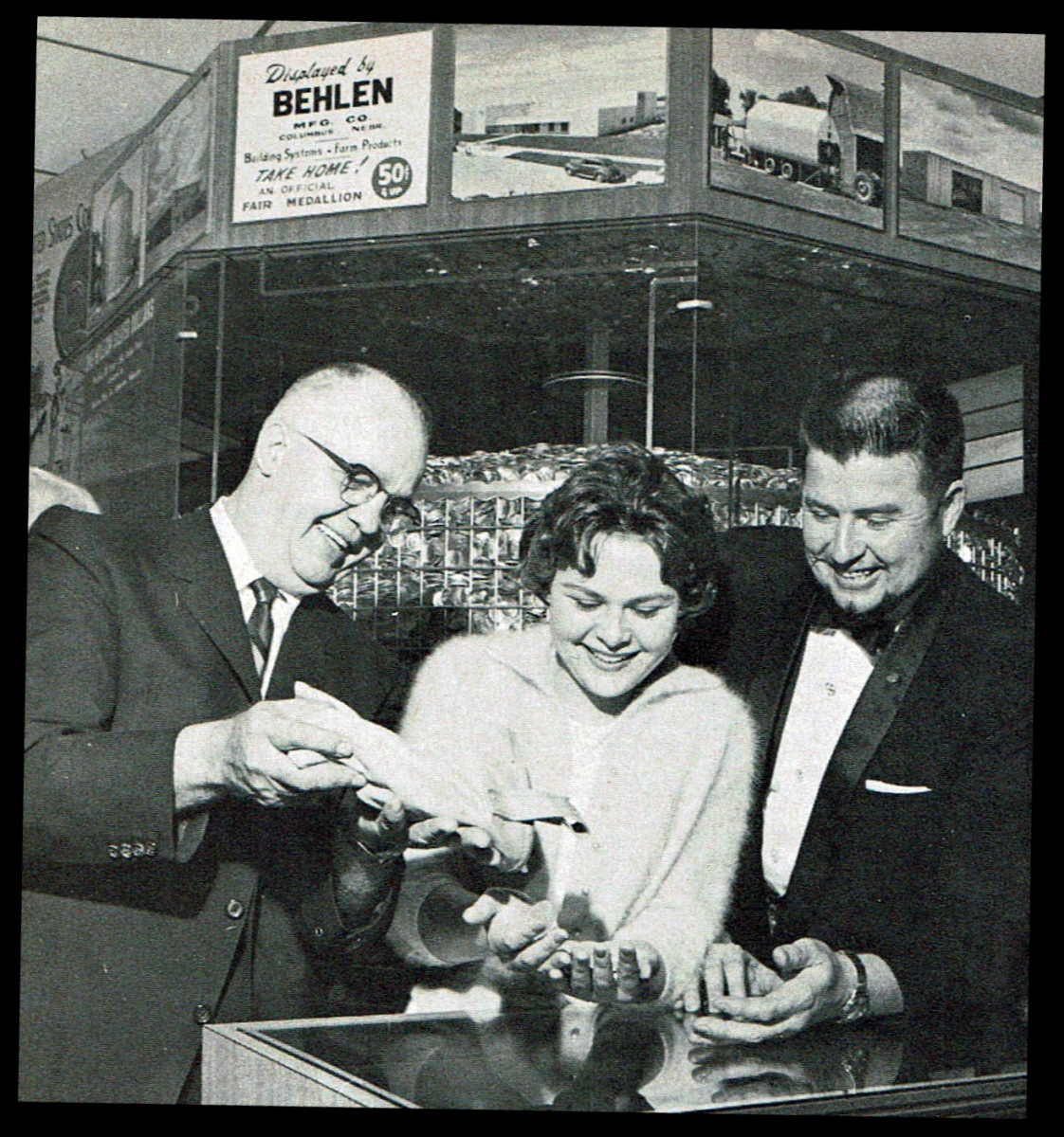 Anne Marbury of Baldwin Park, Calif., was the millionth visitor to the silver dollar display. She received 100 silver dollars from Walter Behlen, left. At right is Barney Tomlinson.